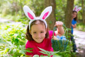 Rapariga com cesto de ovos e orelhas de coelho